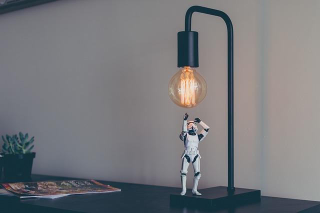 Plastová figúrka, ktorá sa načahuje po žiarovke v čiernej lampe