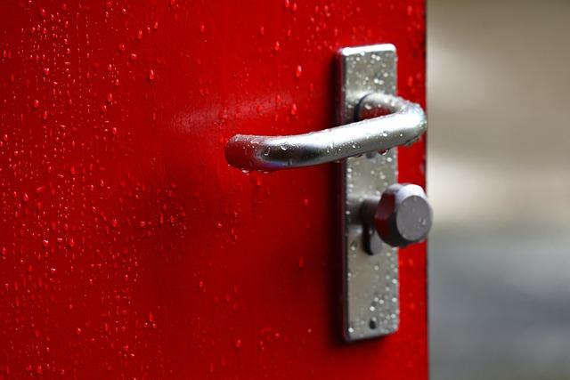 Pootvorené červené dvere so striebornou kľučkou.jpg