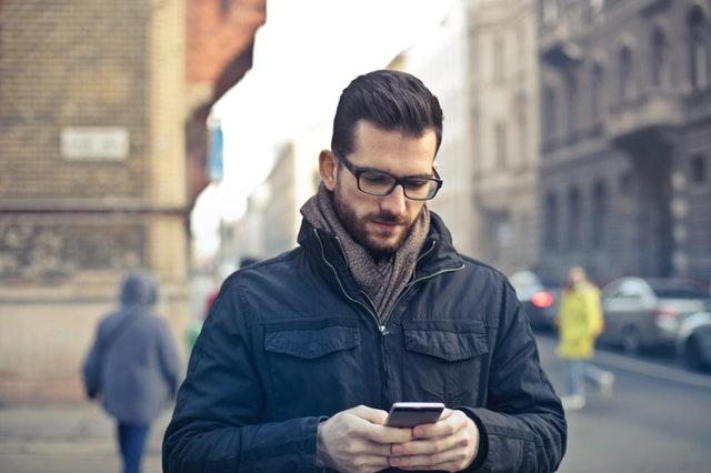 Muž v čiernej ležérnej bunde pozerá do mobilu a ide po ulici