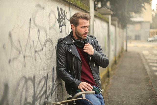 Muž v čiernej koženej bunde stojí vedľa bicyklu a betónovej steny