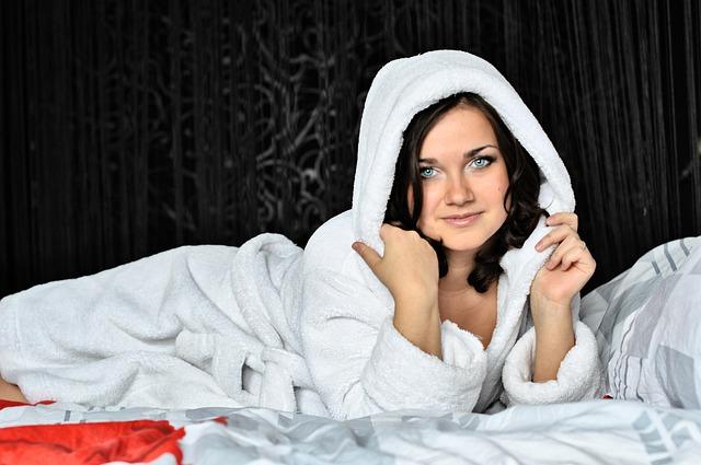 Žena s tmavými vlasmi, modrými očami oblečená v župane leží na posteli ,.jpg