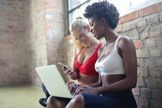 Dve ženy sedia na zemi a pozerajú na počítač